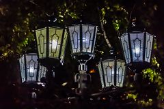 A group of five beautiful street lighting lanterns is against the black sky and green leaves background. Is in a park in the summer evening royalty free stock photo