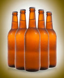 A group of five beer bottles in a diamond formation on color bac Stock Images
