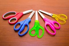 Group of five colored scissors on wood tabble. royalty free stock images