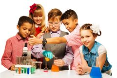 Enjoyment in chemistry class. Group of five diversity kids boys and girls blond and brunet with microscope and test tubes and flasks in chemistry class, isolated Stock Photos