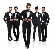 Group of five elegant men with leader buttoning suit. Group of five elegant men wearing black tuxedoes with leader buttoning suit and stepping in front of them royalty free stock images
