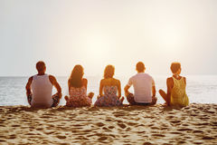 Group of five friends on beach. Group of five friends relaxig on sunset beach. Space for text royalty free stock photo