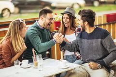 Group of five friends having a coffee together. Two women and two men at cafe talking laughing and enjoying their time using digital tablet stock images