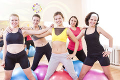Group of Five Happy Caucasian Female Athletes Posing Together Embraced Against Fitballs Royalty Free Stock Photo