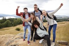 A group of five happy young adult friends cheer at the summit during mountain hike stock photos