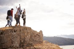 A group of five happy young adult friends cheer with their arms in the air at the summit of a mountain during a hike royalty free stock photos