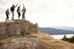 A group of five happy young adult friends cheer with their arms in the air at the summit during mountain hike royalty free stock photo