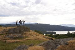 A group of five happy young adult friends cheer with their arms in the air at the summit after a mountain hike royalty free stock image
