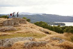 A group of five mixed race young adult friends arrive at summit with arms in the air after a mountain hike royalty free stock images