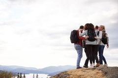 A group of five mixed race young adult friends embrace after arriving at the summit during mountain hike, close up royalty free stock image