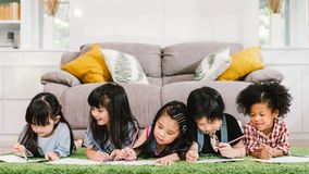 Group of five multi-ethnic young cute preschool kids, boy and girls happy studying or drawing together at home or school royalty free stock photos
