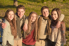 Group of Five Teens Embracing. Cute group of European teenagers embracing each other Stock Photo