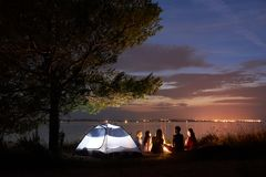 Night summer camping on shore. Group of young tourists around campfire near tent under evening sky. Group of five travellers, girls and boy having a rest on lake stock photos