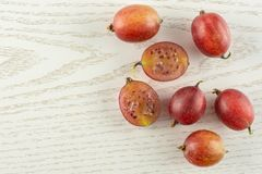 Fresh raw red gooseberry on grey wood. Group of five whole two halves of fresh red gooseberry hinnomaki variety flatlay on grey wood Stock Image