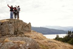 A group of five young adult friends embrace with arms in the air after arriving at summit during mountain hike, back view royalty free stock photo