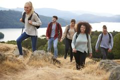 A group of five young adult friends smiling while hiking to a mountain summit stock photography