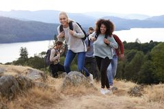 A group of five young adult friends smiling while hiking together to a mountain summit stock photography