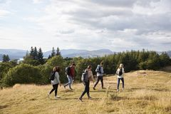 A group of five young adult friends walking on a rural path during a mountain hike, side view royalty free stock photo