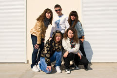 Group of five young people. Five teenagers standing near white background wall Stock Image