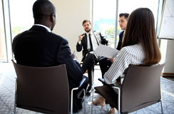 Group of five young people discussing something while sitting at the table in office together Stock Image