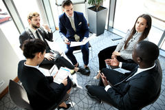 Group of five young people discussing something while sitting at the table in office together Stock Images