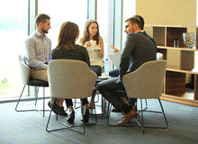 Group of five young people discussing something while sitting at the table in office together. Morning meeting. Group of five young people discussing something Stock Images