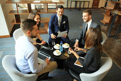 Group of five young people discussing something while sitting at the table in office together. Morning meeting. Group of five young people discussing something Stock Photo