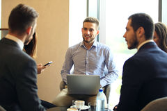 Group of five young people discussing something while sitting at the table in office together. Morning meeting. Group of five young people discussing something Royalty Free Stock Image