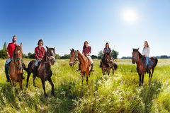 Group of five young people enjoy riding horses. In flowery meadows Stock Image
