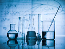 Group of flask on a lab table. Group of laboratory flasks empty or filled with a clear liquid on blue tint scientific graphics background and their reflection on Royalty Free Stock Photography