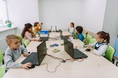Group of focused kids working with computers. On machinery class stock image