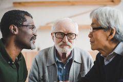 Senior friends playing staring contest. Group of focused multiethnic senior friends playing staring contest Stock Photos
