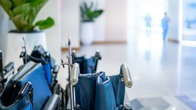 Group of folding wheelchair in hospital. Group of blue folding wheelchair with blurred doctor and nurse walking through the corridor in hospital or medical royalty free stock photos