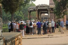 Foreign tourists at Qutub Minar Complex. Group of foreign tourists at Qutub Minar, a UNESCO World Heritage Site located in Mehrauli, Delhi, India Royalty Free Stock Photos