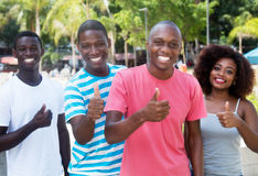 Group of four african american woman and man showing thumb. Group of four african american women and men showing thumb outdoor in the city in the summer Royalty Free Stock Image