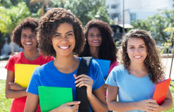 Group of four beautiful brazilian female students. Outdoor in the city in summer Royalty Free Stock Photos