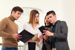 Group of four business people looking at tablet Stock Images