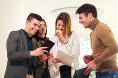 Group of four business people looking at tablet Royalty Free Stock Images