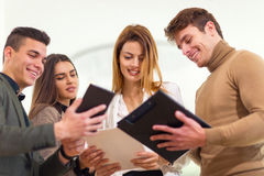 Group of four business people looking at tablet Stock Photo
