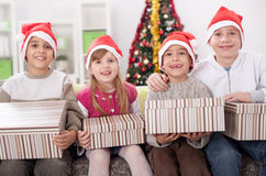 Group of four children in Christmas hat with presents Royalty Free Stock Images