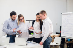 Group of four diverse men and women in casual clothing talking in office Royalty Free Stock Photos
