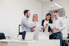 Group of four diverse men and women in casual clothing talking in office Stock Photography