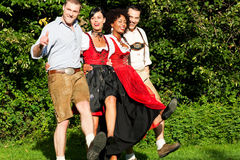 Group of four friends in Bavarian Tracht dancing Royalty Free Stock Image