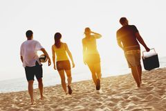 Group four friends beach picknik sunset sea. Group of four friends going to the beach picknik on sunset sea Stock Image