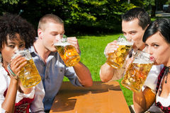 Group of four friends in beer garden Royalty Free Stock Photography