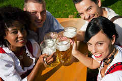 Group of four friends in beer garden. Group of four people in Couple in traditional Bavarian dress, Lederhosen and Dirndl (only parts of body to be seen), in a Stock Photo