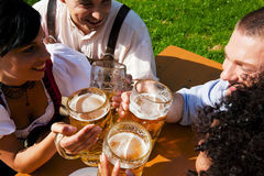 Group of four friends in beer garden. Group of four people - two Couples - in traditional Bavarian dress, Lederhosen and Dirndl, in a beer garden royalty free stock photography