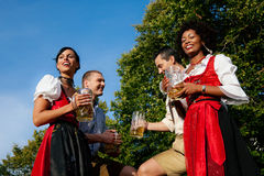 Group of four friends in beer garden royalty free stock photos