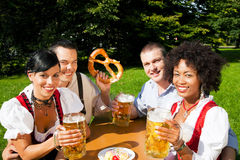 Group of four friends in beer garden eating. Group of four people - two Couples - in traditional Bavarian dress, Lederhosen and Dirndl, in a beer garden with stock photos