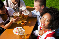 Group of four friends in beer garden eating and dr. Group of four people - two Couples - in traditional Bavarian dress, Lederhosen and Dirndl, in a beer garden royalty free stock photo